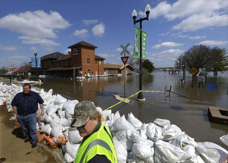Peoria Maintenance Engineer Jim Clark, right bottom, monitors the sand bag wall holding back the Illinois River from recent flooding Wednesday, April 24, 2013, in Peoria, Ill. The Illinois River finally crested Tuesday at 29.35 feet, eclipsing a 70-year record in Peoria. (Seth Perlman/AP)