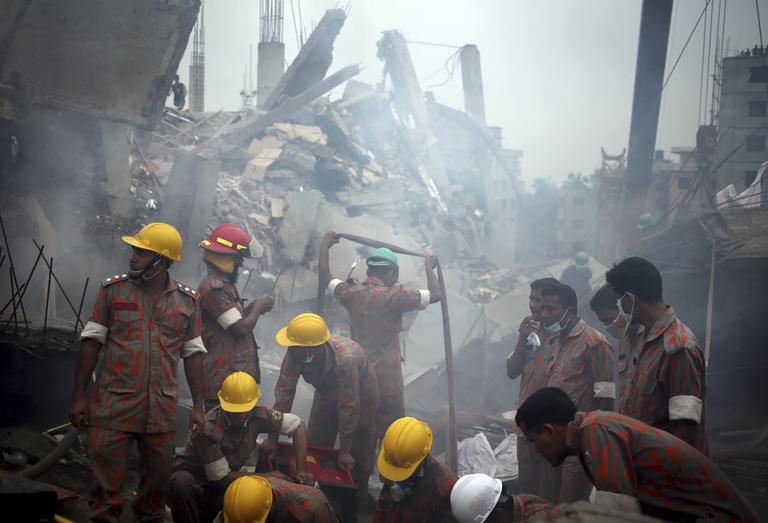 Workers and firefighters are shrouded in smoke as they prepare to dislodge the debris and fallen ceiling of the garment factory building in Savar, Bangladesh, on Monday, April 29, 2013. (Wong Maye-E/AP)