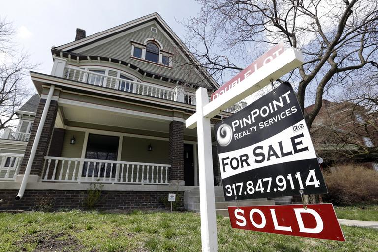 "A ""Sold"" sign is posted outside a home in Indianapolis, Tuesday, April 9, 2013. (Michael Conroy/AP)"