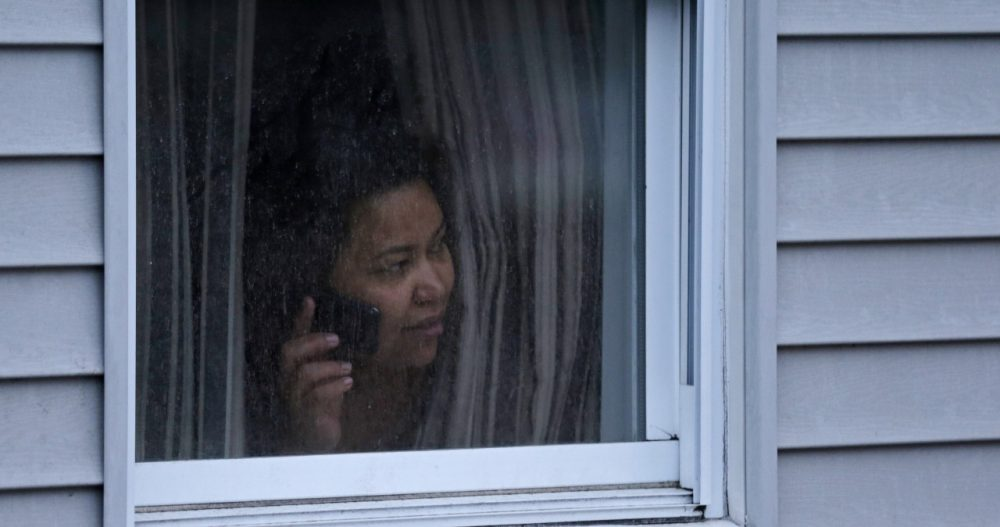 A woman looks out her window in Watertown during the manhunt for the surviving Boston Marathon bombing suspect, on April 19, 2013. (Charles Krupa/AP)