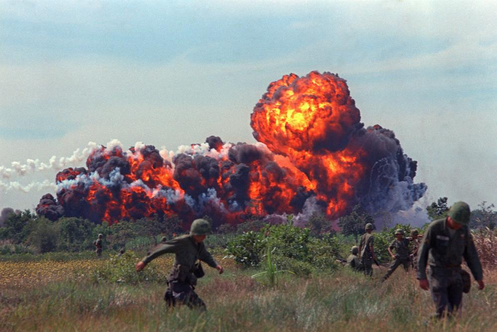 A napalm strike erupts in a fireball near U.S. troops on patrol in South Vietnam, 1966 during the Vietnam War. (AP)
