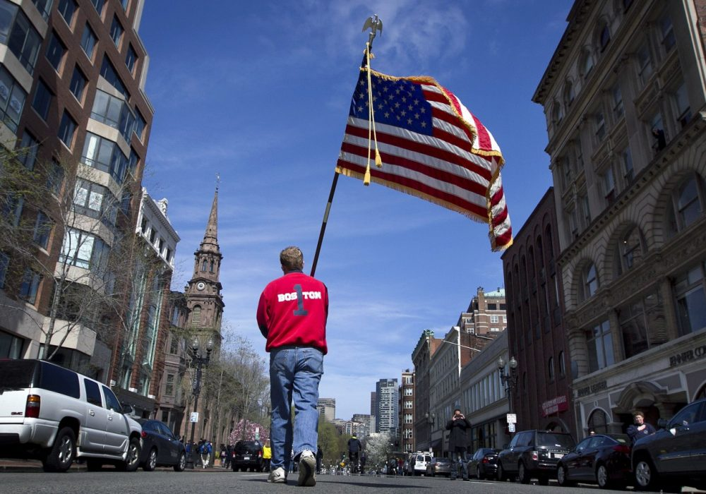 Lt. Mike Murphy of the Newton, Mass., fire dept., carries an American flag down the middle of Boylston Street. (Robert F. Bukaty/AP)