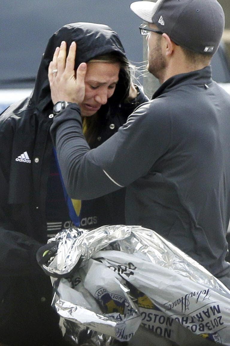 An unidentified Boston Marathon runner is comforted as she cries.(Elise Amendola/AP)