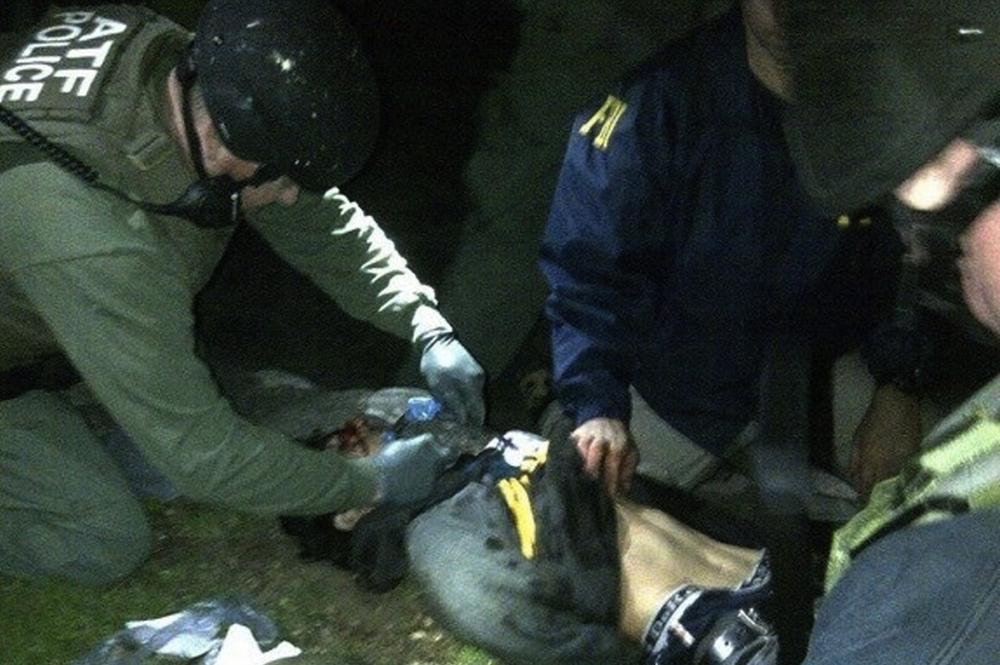 ATF and FBI agents check suspect Dzhokhar Tsarnaev for explosives and also give him medical attention after he was apprehended in Watertown, Mass. on Friday, April 19, 2013. (AP)