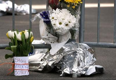 Flowers sit at a police barrier near the finish line of the Boston Marathon in Boston Tuesday, April 16, 2013. (AP Photo/Winslow Townson)