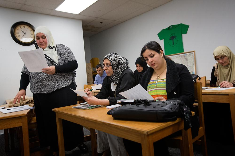 An ESL class reads English phrases at the Iraqi and Arab Community Association In Lynn. (Jesse Costa/WBUR)