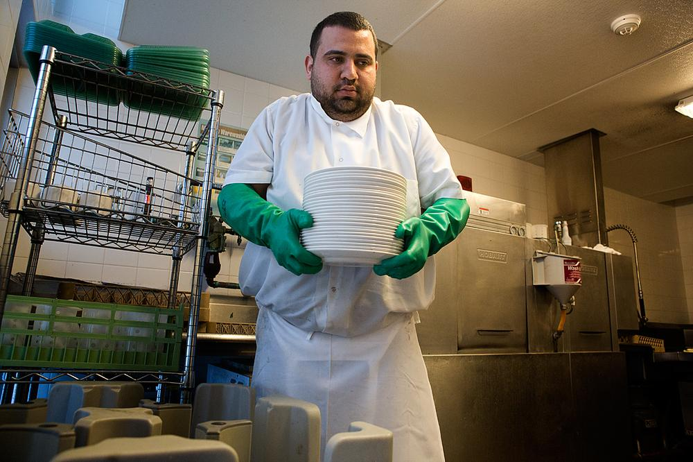 Anas al-Hamdani moves clean dishes into the dining hall at MIT's Simmons Hall. (Jesse Costa/WBUR)