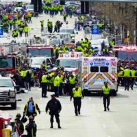 Police clear the area at the finish line of the 2013 Boston Marathon as medical workers help injured following the explosions. (Charles Krupa/AP)