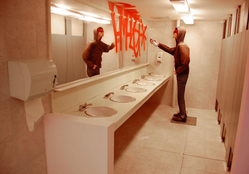 "An animatronic John Lazcano sprays ""Amaze*"" on a bathroom mirror in this 2005/2012 McGee installation. (Greg Cook)"