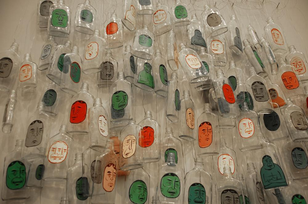 Barry McGee painted faces on booze bottles for this 1999-2005/2012 installation. (Greg Cook)