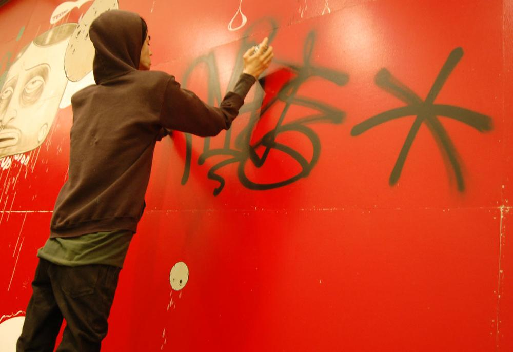 """A robot mannequin depicts Barry McGee's longtime collaborator Josh Lazcano tagging """"Amaze"""" on the ICA's wall. (Greg Cook)"""