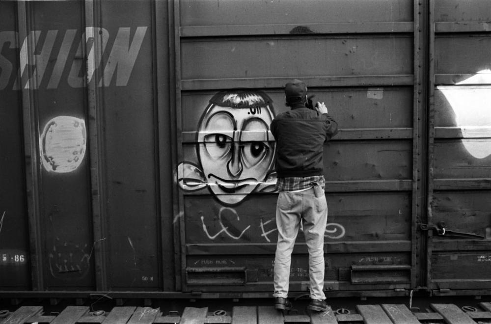 Barry McGee tagging in a train yard in 1993 (Craig Costello/Courtesy ICA)