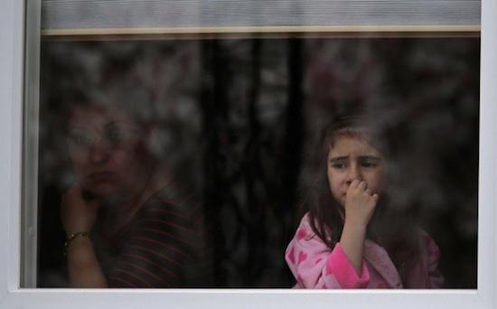 A girl looks out the window of her family's home as a SWAT team drives through her neighborhood while searching for a suspect in the Boston Marathon bombings in Watertown, Mass., Friday, April 19, 2013. (AP Photo/Charles Krupa)