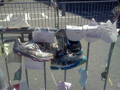Running shoes are tied to one of the barricades around the Boston Marathon bombing crime scene, in a makeshift memorial to victims, pictured on Sunday. (Karyn Miller-Medzon/Here & Now)