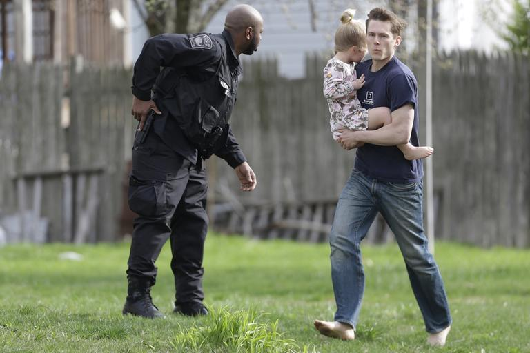 A police officer evacuates a shoeless man holding a child as members of law enforcement continue to search for the bombing suspect in Watertown Friday morning. (Matt Rourke/AP)