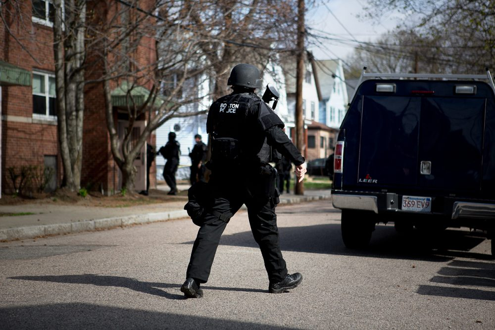 Officers looking for Dzhokhar Tsarnaev move in to search an apartment building on Melendy Avenue in Watertown in 2013. (Jesse Costa/WBUR)