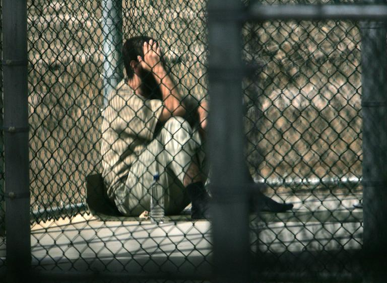 A Guantanamo detainee sits alone inside a fenced area during his daily outside period, at Guantanamo Bay U.S. Naval Base, Cuba. (Brennan LinsleyAP)