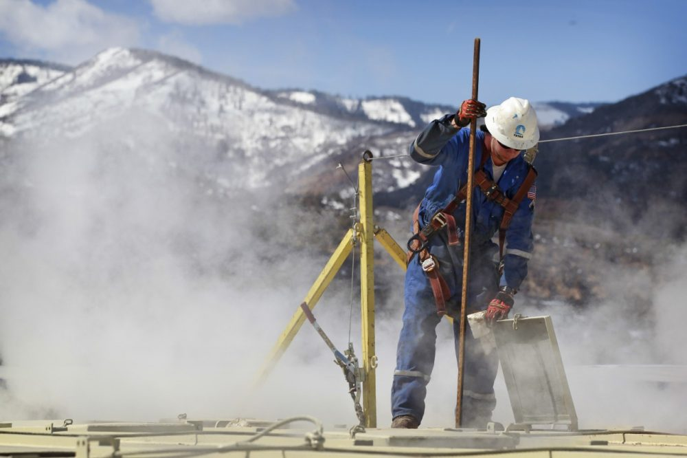 A worker checks a dipstick at an Encana Oil & Gas (USA) Inc. hydraulic fracturing operation at a gas drilling site outside Rifle, Colorado. (AP)