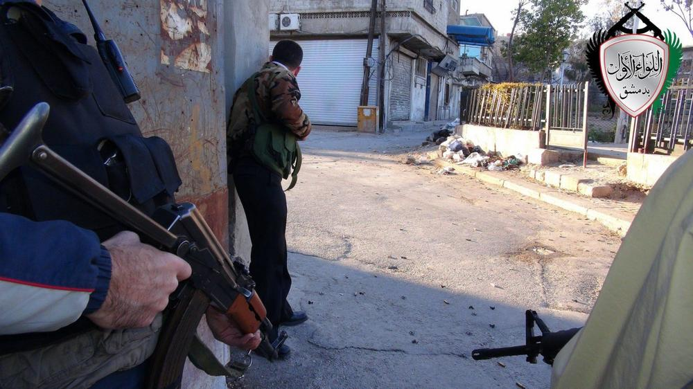 This citizen journalism image shows Syrian rebels taking cover in the the Barzeh district of Damascus, Syria.(AP/Local Council of Barzeh)