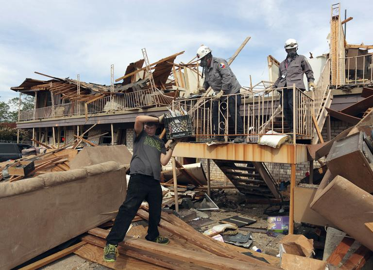 In this photo provided by the Texas Parks & Wildlife Department, Lucas Lambert, left, removes belongings from his mother's residence in the apartment complex destroyed by a fertilizer plant explosion in West, Texas, Saturday, April 27, 2012. (Earl Nottingham/Texas Parks & Wildlife Department via AP)