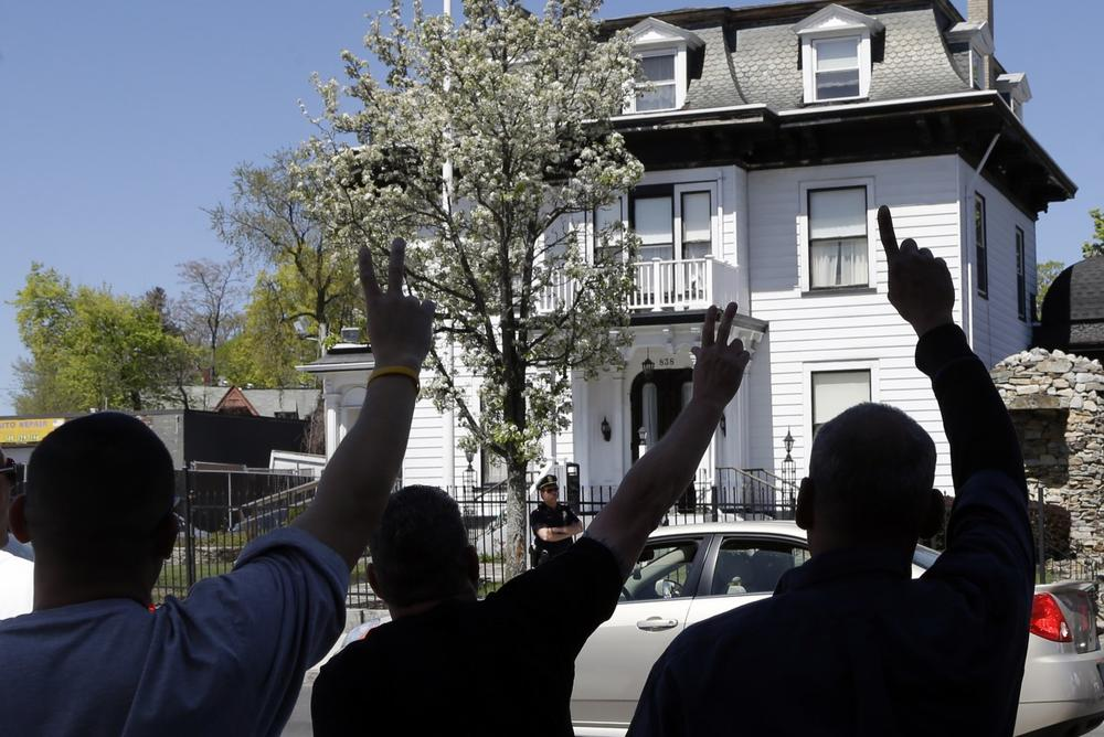 Protesters gesture outside the Graham, Putnam, and Mahoney Funeral Parlors in Worcester, Mass., Monday, where the body of killed Boston Marathon bombing suspect Tamerlan Tsarnaev is being prepared for burial. (AP)