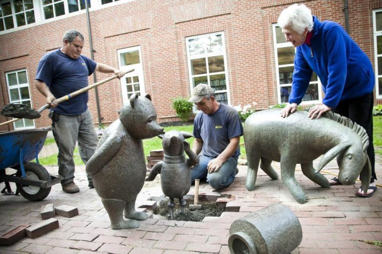 Sculptor Nancy Schön oversees the installation of Piglet at the Newton Free Library. (Courtesy of Jacki Schon)