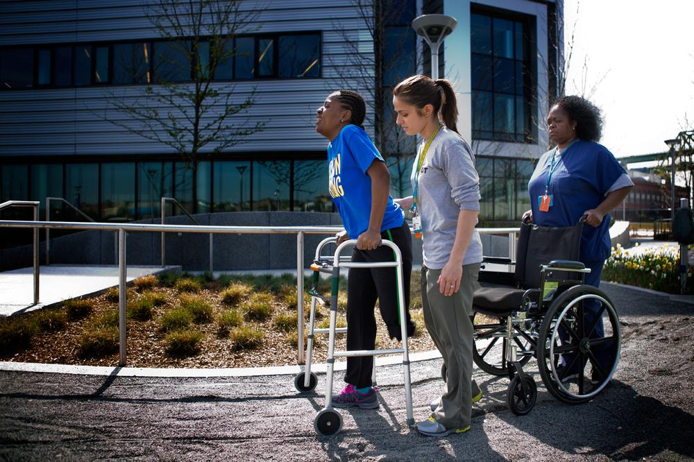 Daniel works with occupational therapist Becky Buttiglieri and Teresa Ashmead outside of Spaulding. (Jesse Costa/WBUR)