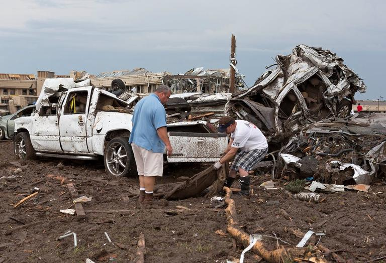 Two men go through the damage surrounding the Moore Medical Center and damaged vehicles after a tornado moved through Moore, Okla. on Monday, May 20, 2013. (Alonzo Adams/AP)