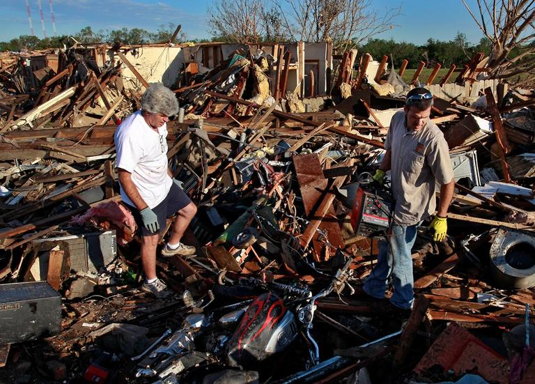Chad Brown, right, helps his father Rick sift through the wreckage of his home in a neighborhood which was destroyed Monday when a tornado moved through Moore, Okla., Wednesday, May 22, 2013. (Brennan Linsley/AP)