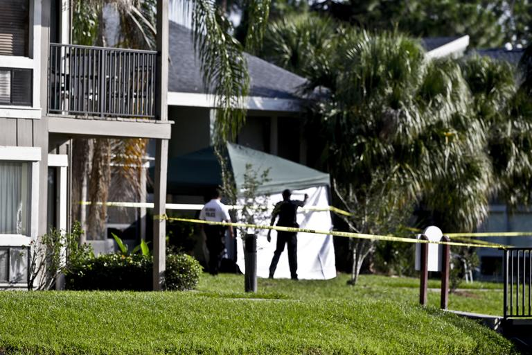 Investigators stand outside an apartment complex in Orlando, Fla., where on Wednesday a man being questioned by authorities in the Boston bombing probe was fatally shot when he initiated a violent confrontation, FBI officials said. (John Raoux/AP)
