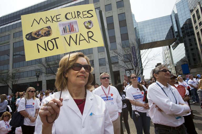 "Lorraine Gudas, chair of pharmacology at Weill Cornell Medical College, participates in a ""Rally for Medical Research,"" Monday, April 8, 2013, in Washington. The rally focused on sequestration's cuts to NIH funding, impacting patients, jobs and research. (Jacquelyn Martin/AP)"