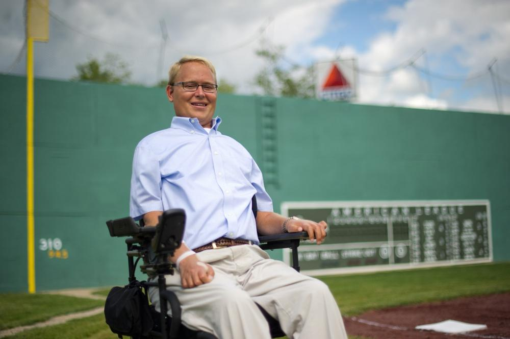 "Travis Roy, the namesake of the Travis Roy Foundation, sits by third base at ""Little Fenway"", which is modeled after Boston's Fenway Park, before a charity Wiffle Ball tournament to benefit the Foundation in Essex, Vt., on Friday, August 12, 2011. (Andy Duback/AP)"