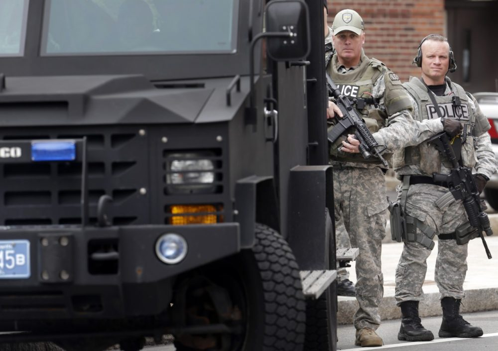 Members of a police SWAT team hold rifles while standing next to an armored vehicle outside an entrance to a memorial service for fallen Massachusetts Institute of Technology police officer Sean Collier, in Cambridge, Mass., Wednesday, April 24, 2013. Collier was fatally shot on the MIT campus Thursday, April 18, 2013. Authorities allege that the Boston Marathon bombing suspects were responsible. (AP Photo/Steven Senne)