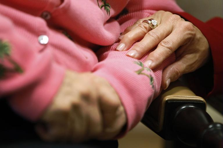 Alexis McKenzie, right, executive director of The Methodist Home of the District of Columbia Forest Side, an Alzheimer's assisted-living facility, puts her hand on the arm of resident Catherine Peake, in Washington, Monday, Feb. 6, 2012. (AP)