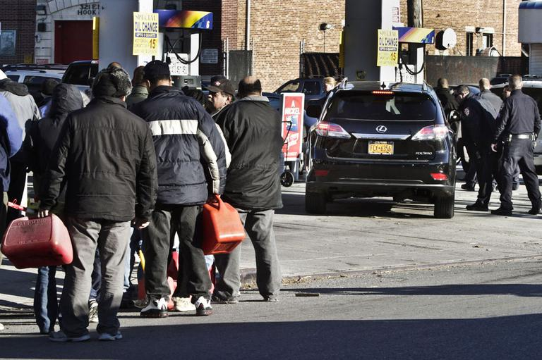 Police direct cars to pumps while people stand in line with containers for gas in the wake of Superstorm Sandy, on Friday, Nov. 9, 2012 in the Brooklyn borough of New York. Police were at gas stations to enforce a new gasoline rationing plan that lets motorists fill up every other day. (AP)