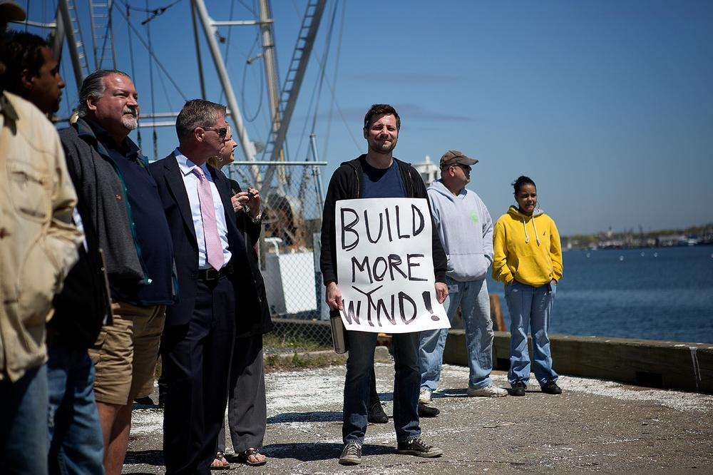 """A man with a sign reading """"Build more wind!"""" attends the ground-breaking ceremony for the New Bedford Marine Commerce Terminal. (Jesse Costa/WBUR)"""