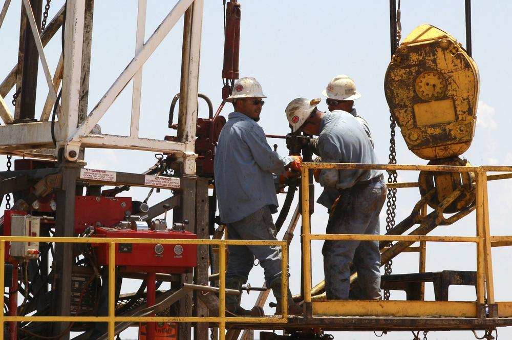 In this Friday, July 20, 2012 photo, workers are pictured on a drilling rig near Calumet, Okla. Oklahoma is one of several states, including North and South Dakota, that has enjoyed a boom in the energy sector. (Sue Ogrocki/AP)