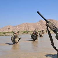 In this April 10, 2013 photo released by the U.S. Army, U.S. Soldiers with Charlie Company, 1st Battalion, 38th Infantry Regiment, 4th Brigade Combat Team, 2nd Infantry Division cross the Tarnak river in the Panjwai district of Kandahar province, Afghanistan on a two-day mission to clear the area of explosives caches. (Sgt. Kimberly Hackbarth, U.S. Army/AP)