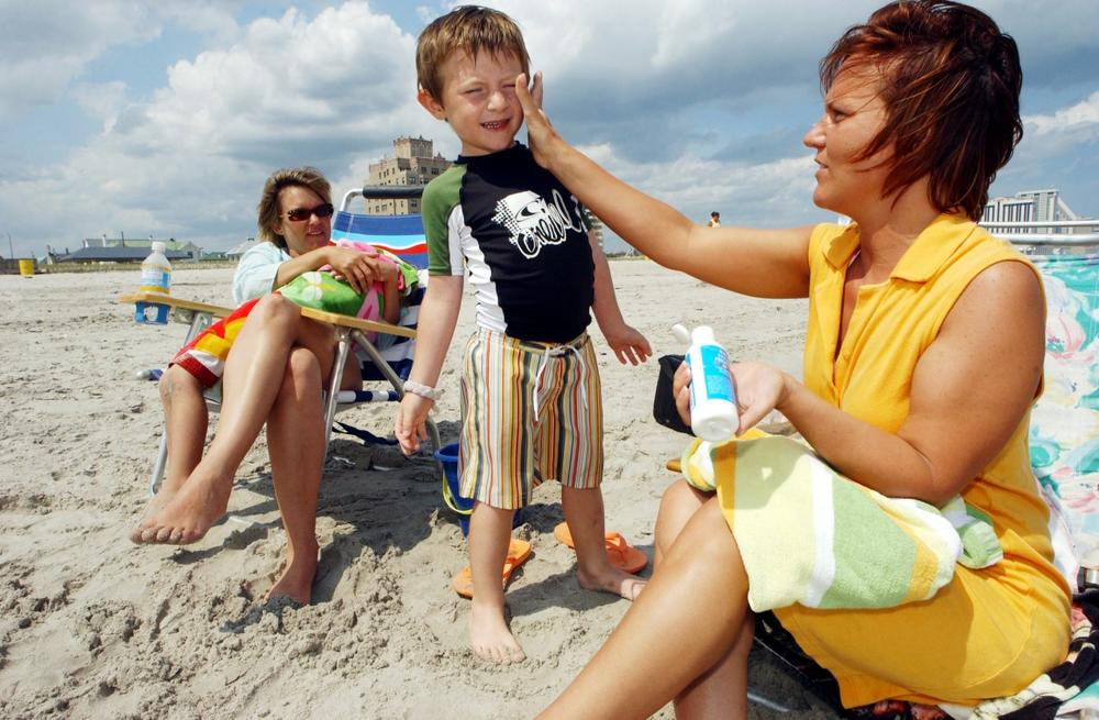 Bernadine Boyce, of Allentown, Pa., applies sunscreen to Bruno Barber, 5, of Atlantic City, as mom, Natalia Barber, watches in Atlantic City, N.J., in June 2006. (Mary Godleski/AP)