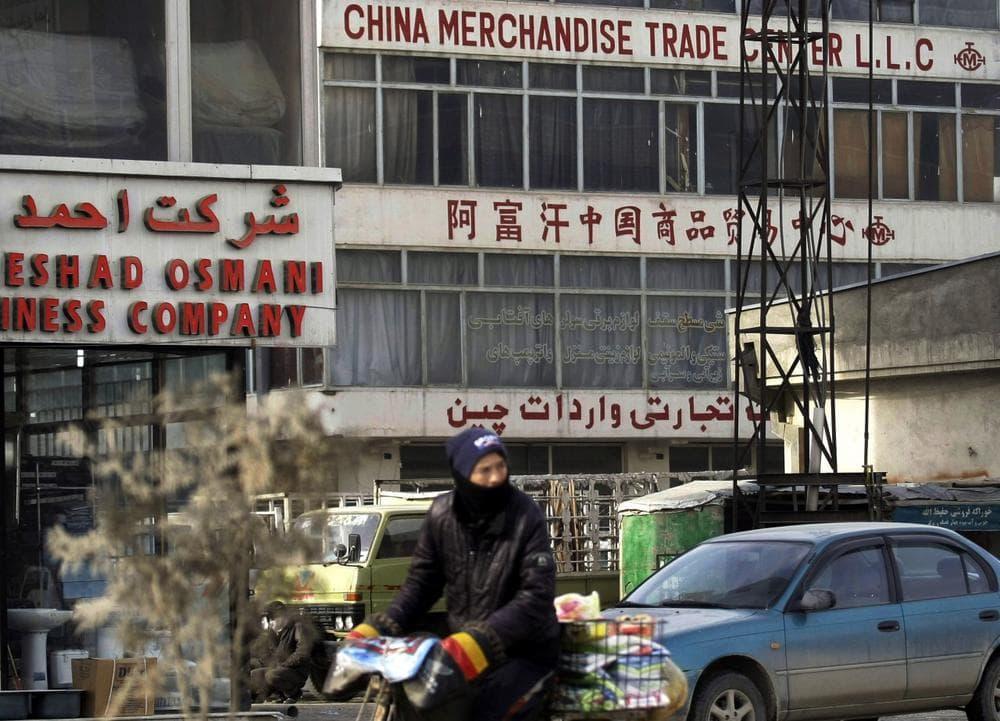 An Afghan man rides his bike past a China Merchandise Trade Center in Kabul, Afghanistan, Jan. 22, 2013. (Musadeq Sadeq/AP)
