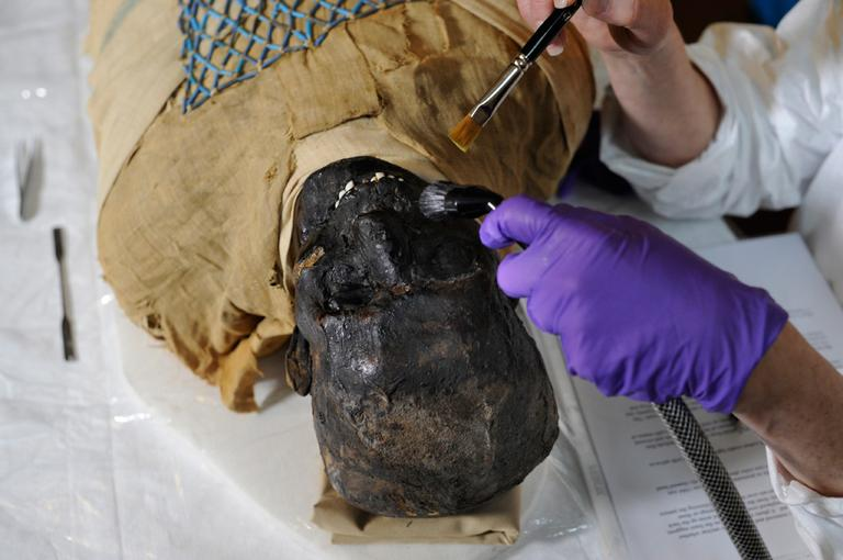 Mimi Leveque, a freelance conservator, cleans Padihershef, a 2,500-year-old Egyptian mummy, at Mass. General Hospital on Friday. (Gretchen Ertl/AP)