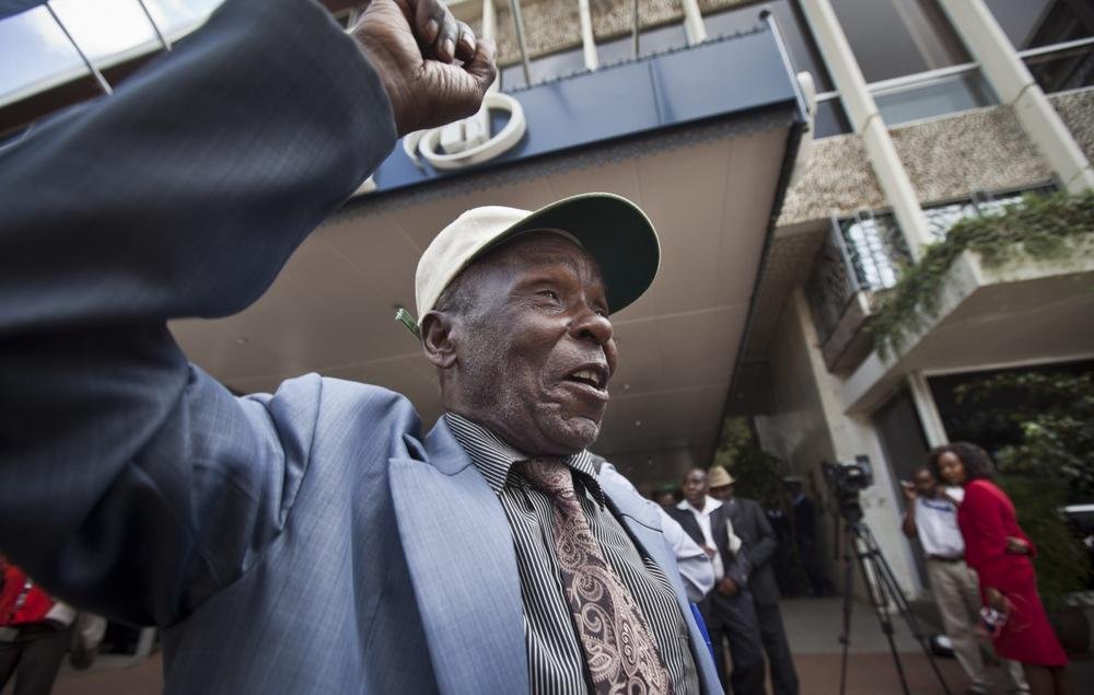 An elderly Mau Mau veteran raises his fist in the air to celebrate as he leaves a press conference announcing a settlement in their legal case for compensation against the British Government, in Nairobi, Kenya Thursday, June 6, 2013. (Ben Curtis/AP)