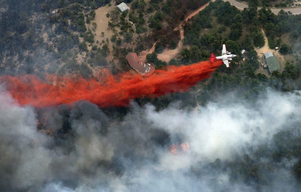 Black Forest Fire Dept. officers burn off natural ground fuel in an evacuated neighborhood, prepping the area for the encroachment of the wildfire in the Black Forest area north of Colorado Springs, Colo., on Wednesday, June 12, 2013. (Brennan Linsley/AP)