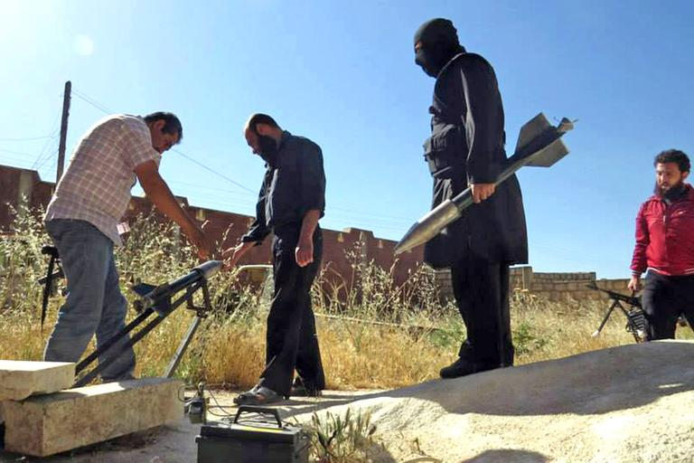 This Tuesday, June 4, 2013 citizen journalism image provided by Edlib News Network, which has been authenticated based on its contents and other AP reporting, shows Syrian rebels preparing to fire locally made rockets in Idlib province in northern Syria. (Edlib News Network/AP File)
