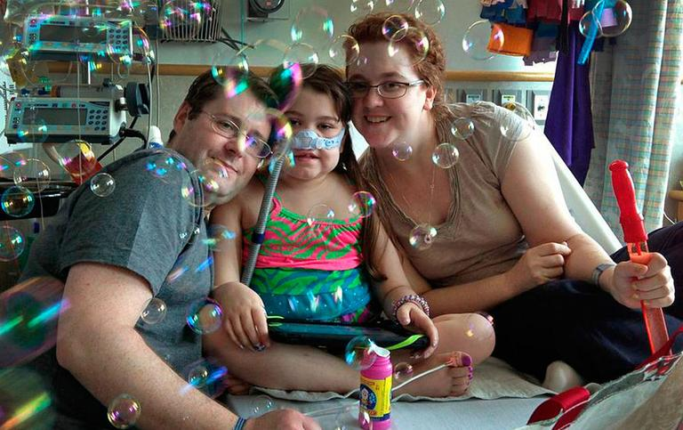 Sarah Murnaghan, center, celebrates the 100th day of her stay in Children's Hospital of Philadelphia with her father, Fran, left, and mother, Janet. (AP Photo/Murnaghan Family)