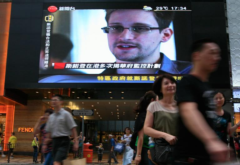 """A TV screen shows a news report of Edward Snowden, a former CIA employee who leaked top-secret documents about sweeping U.S. surveillance programs, at a shopping mall in Hong Kong Sunday, June 23, 2013. The former National Security Agency contractor wanted by the United States for revealing two highly classified surveillance programs has been allowed to leave for a """"third country"""" because a U.S. extradition request did not fully comply with Hong Kong law, the territory's government said Sunday. (Vincent Yu/AP)"""
