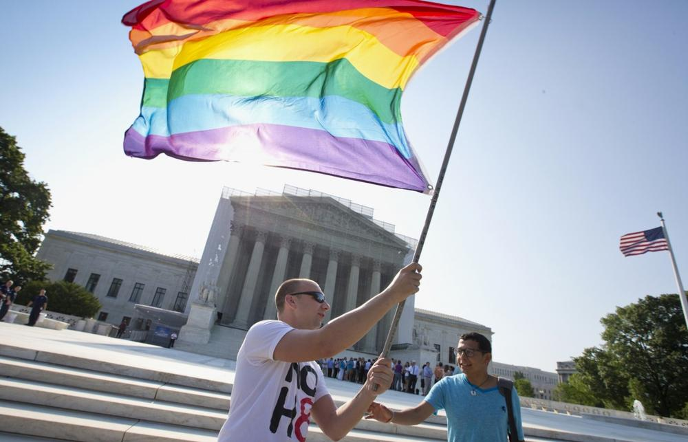 Vin Testa of Washington waves a rainbow flag in support of gay rights outside the Supreme Court in Washington, Tuesday, June 25, 2013, as key decisions are expected to be announced. (J. Scott Applewhite/AP)