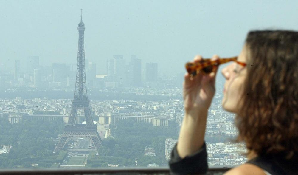 An unidentified woman puts on sunglasses as she looks at the Eiffel Tower under a heat haze in Paris, August, 2003. (Franck Prevel/AP)