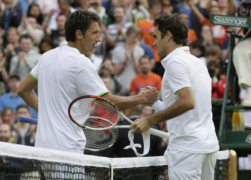 Sergiy Stakhovsky is congratulated by Roger Federer after ousting the tennis legend in the second round at Wimbledon. (Alistair Grant/AP)