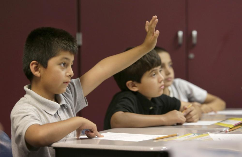 A student raises his hand to be called on while doing a worksheet in an English Language Learner summer school class at the Cordova Villa Elementary School in Rancho Cordova, CA. (Rich Pedroncelli/AP)